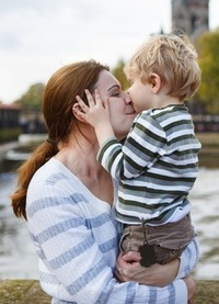 Adorable little son and mother in autumn city.