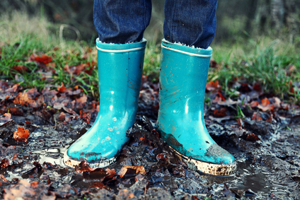 Fall / Autumn concept - Rain boots in mud puddle